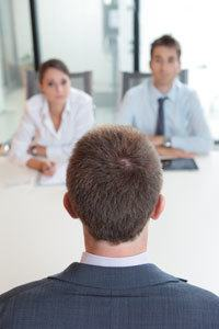 Two business people having job interview with young man